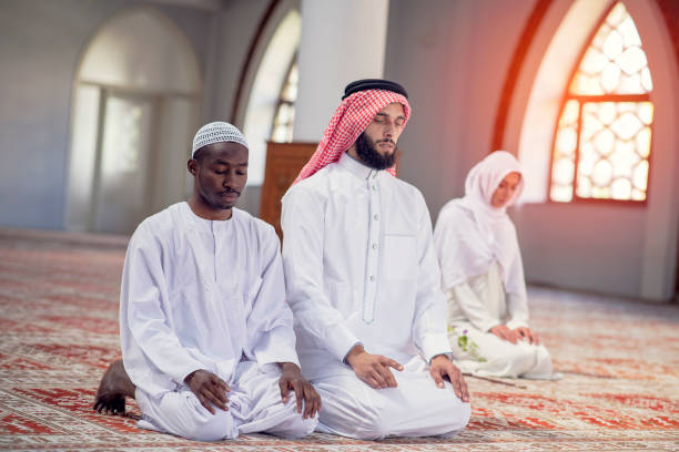 Muslim Couple Praying inside of beautiful mosque stock photo
