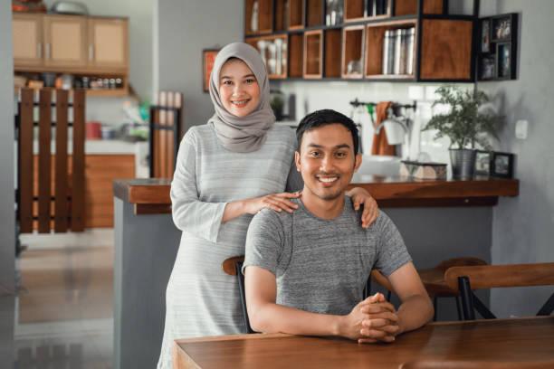 couple musulman assis dans la salle à manger ensemble - mariage musulman photos et images de collection