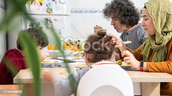 Muslim family with two children having iftar dinner on dining table. Woman with headscarf, husband, daughter and son are seen in frame. Shot indoor with a full frame mirrorless camera.