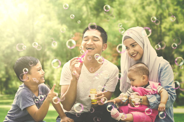 Muslim family playing with soap bubble stock photo