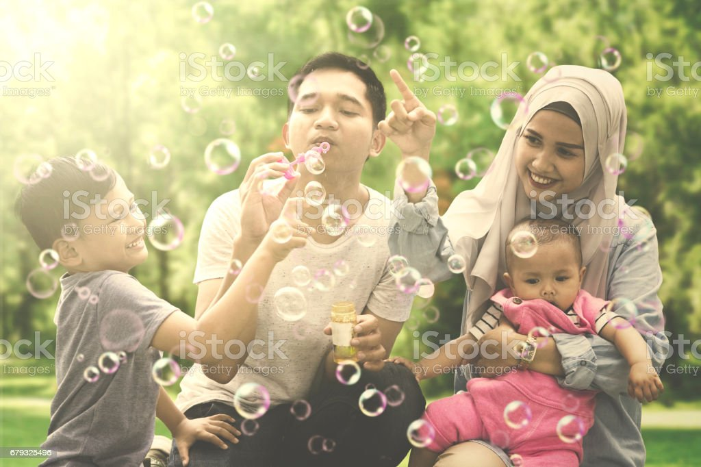 Muslim family playing with soap bubbles royalty-free stock photo
