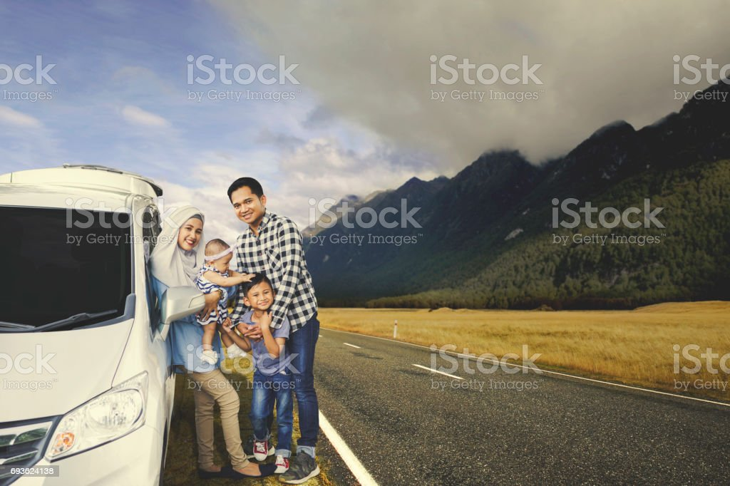 Muslim family resting near their car stock photo