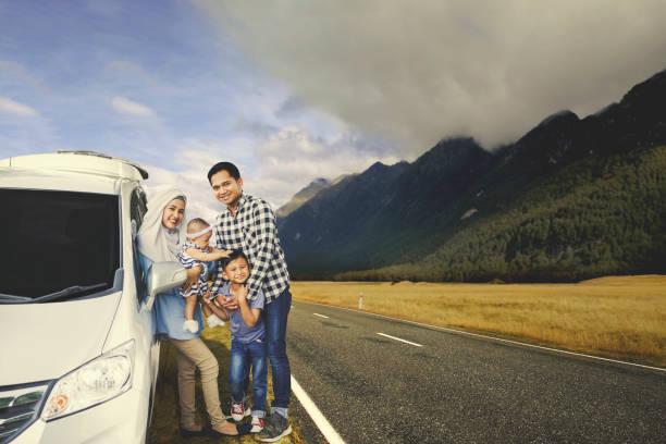 Muslim family resting near their car stock photo
