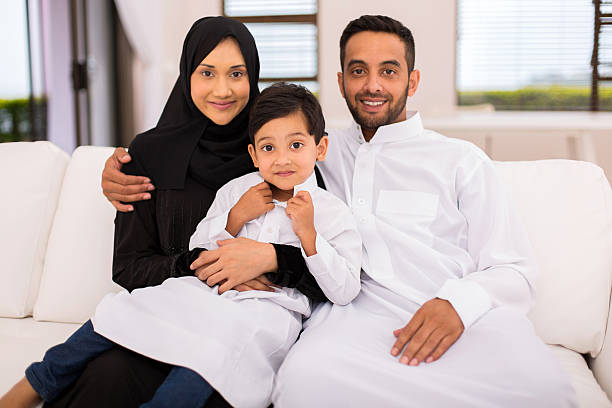 muslim family sitting on the couch stock photo