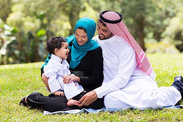 muslim family sitting outdoors stock photo