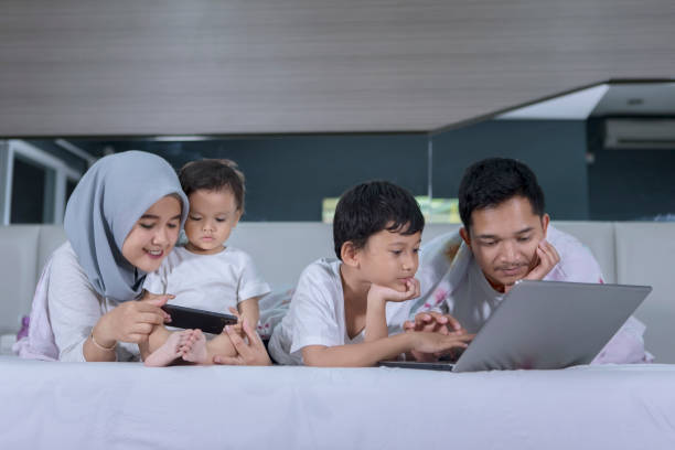 Muslim family using digital device on the bed stock photo