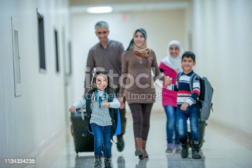 A beautiful muslim family walks down the corridor to board their plane. They are excited and all smiling.