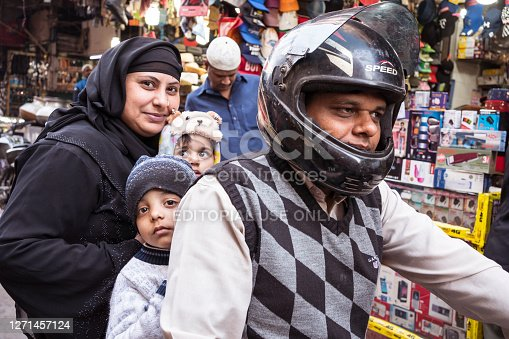 New Delhi / India - February 18, 2020: Muslim family with children and Muslim woman with hijab riding motorcycle in narrow streets of Old Delhi