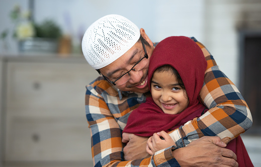 An adorable Muslim little girl is being embraced by her father. She appears to be smiling and happy.