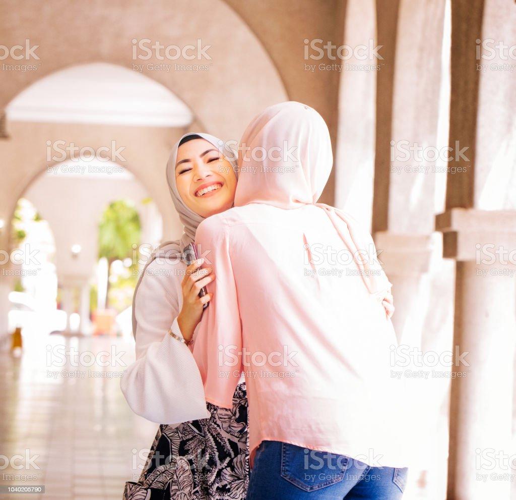 aa304e29b940 Muslimische Frauen Collegestudent Genießen Eine Willkommene Umarmung ...