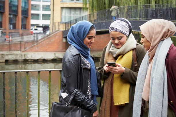 muslim female friends using mobile phone in urban setting - скромная одежда стоковые фото и изображения