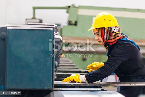 muslim female worker working on cutting machine