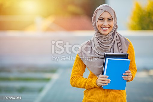 Muslim girl, a college student, holding her workbooks at student campus. Muslim woman with notebooks. Young Student wearing a veil and holding a copybook