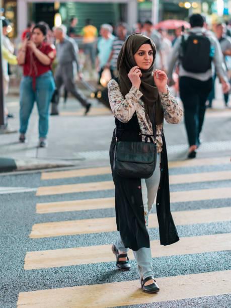 Muslim Girl Crossing Street stock photo