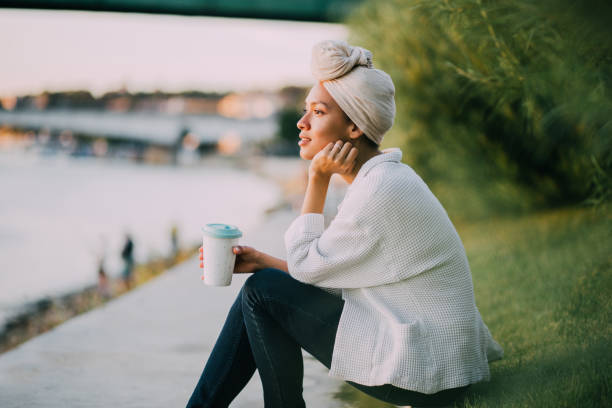 Muslim girl enjoying coffee by a river Muslim girl with a scarf having a cup of coffee by the river women's issues stock pictures, royalty-free photos & images