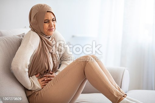 Food Poisoning Concept. Sick Muslim Girl In Hijab Having Acute Abdominal Pain, Suffering From Cramps, Sitting On Sofa At Home Holding Belly. Muslim girl in hijab having stomach ache