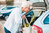 Young Muslim girl putting reusable shopping bags with groceries into car trunk