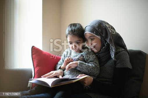A young Muslim girl dressed casually and wearing a Hijab, sits on a sofa reading a book to her younger sister.  The little girl is sitting on her sisters lap as they enjoy the storybook together.