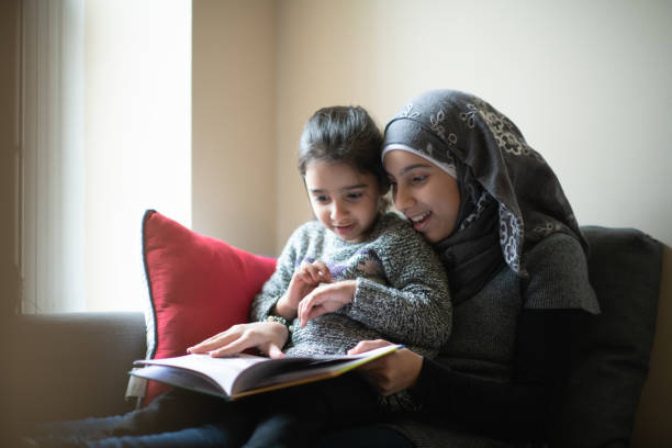 Muslim Girl Reading to Her Sister stock photo stock photo