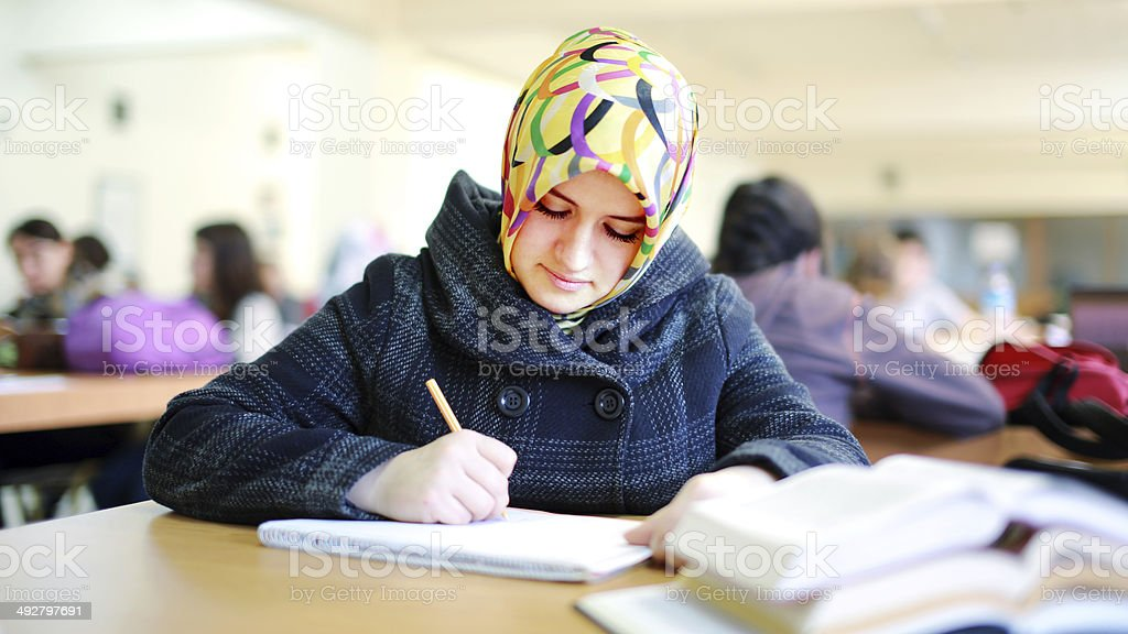 Muslim girl studying in library stock photo