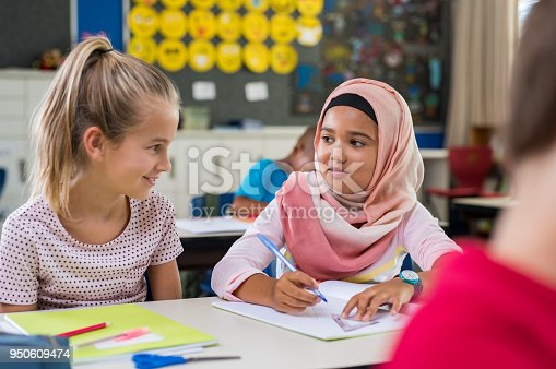 istock Muslim girl with her classmate 950609474