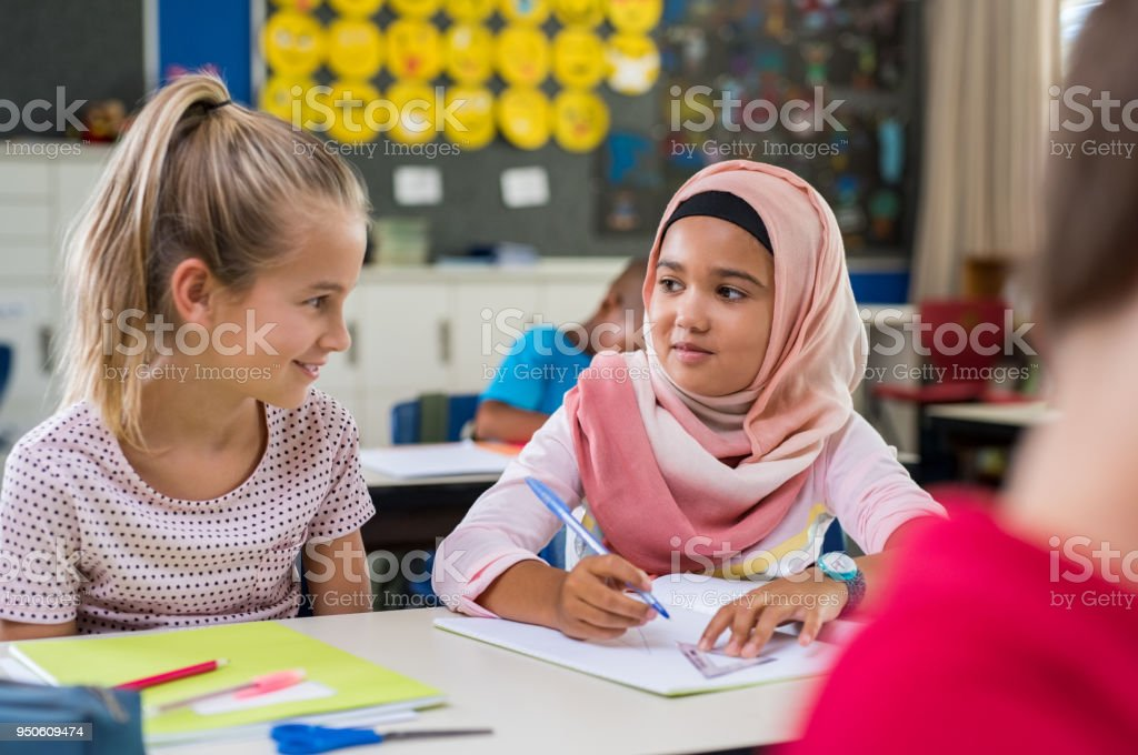 Muslim girl with her classmate stock photo