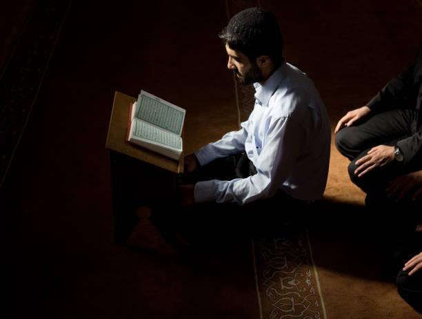 muslimische imam lesung qoran bei-moschee - geführtes lesen stock-fotos und bilder