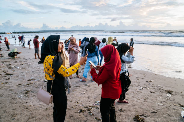Muslim Indonesian women meeting a sunset on the Kuta beach, Bali. stock photo