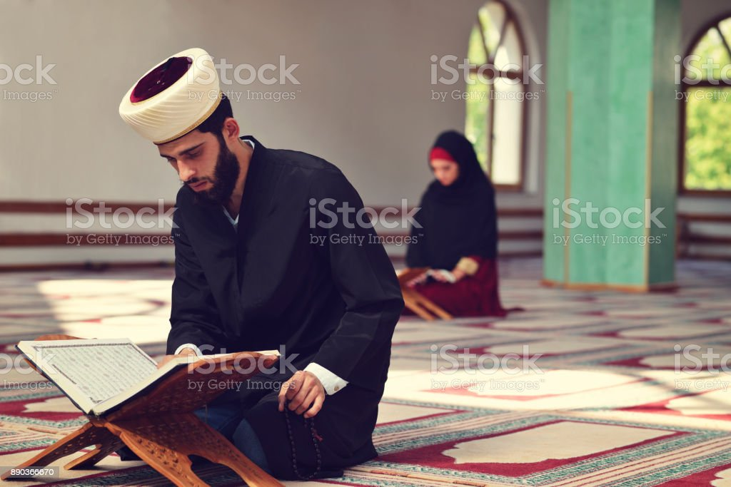 Muslim man and woman praying for Allah in the mosque together stock photo