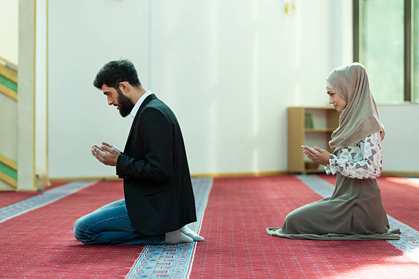 Muslim man and woman praying in mosque - Photo