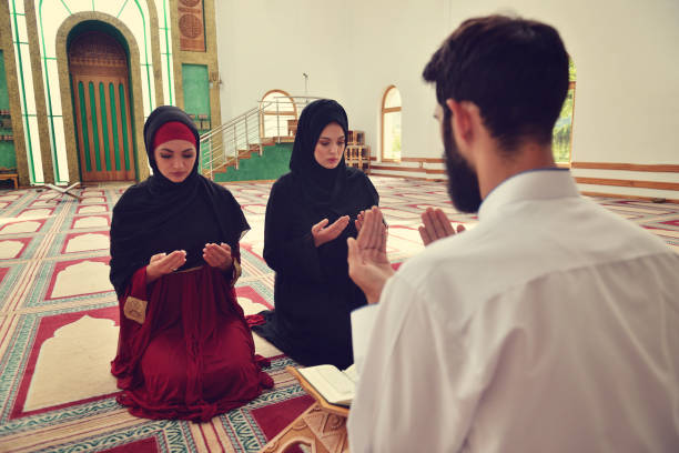 Muslim man and woman praying in mosque stock photo