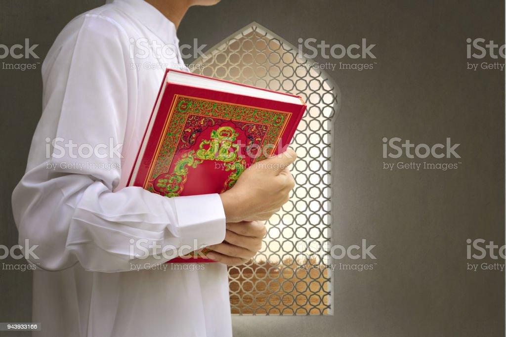 Muslim man bringing the Koran on his hand stock photo