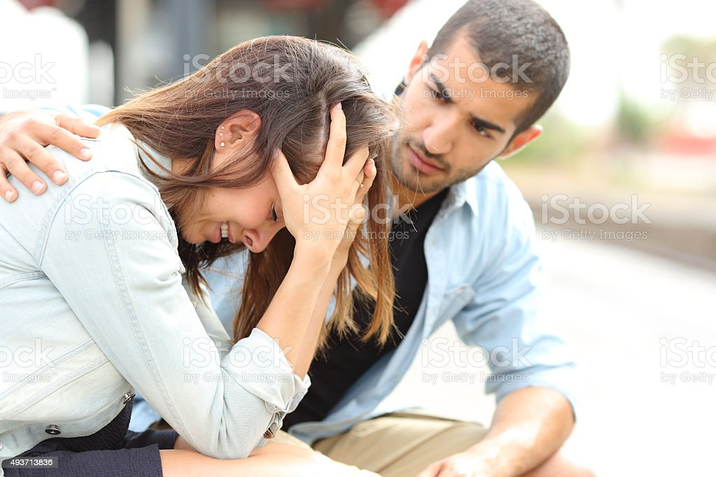 Muslim man comforting a sad girl mourning stock photo