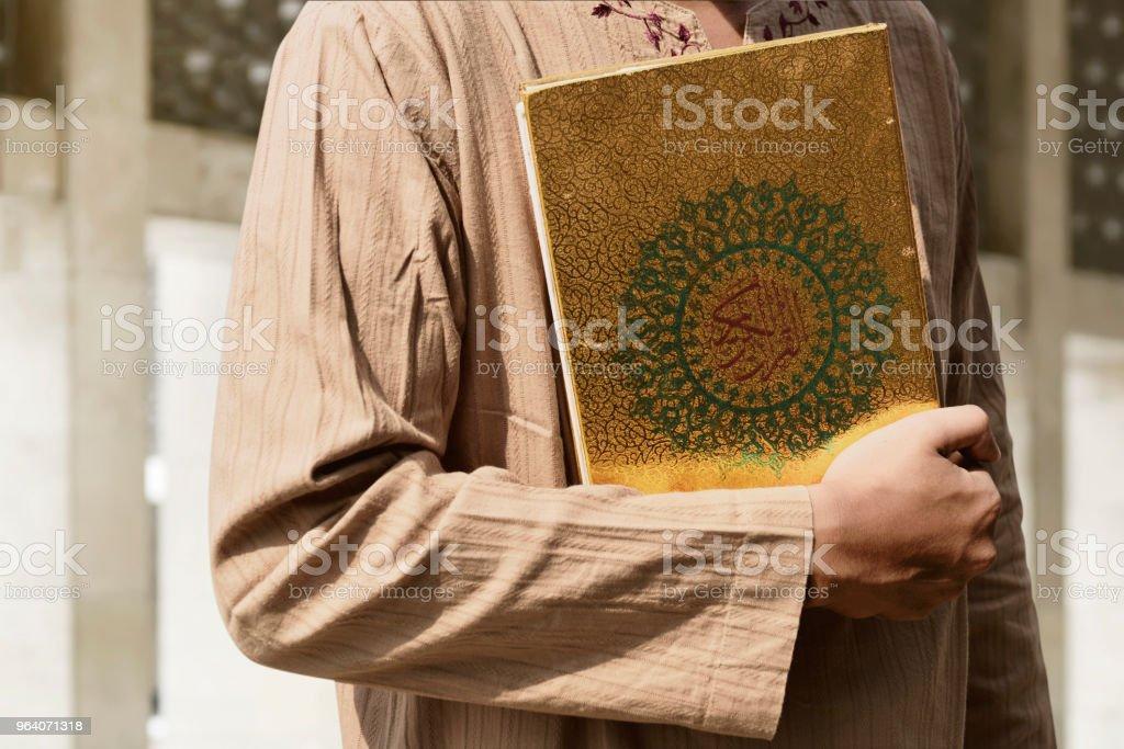 イスラム教徒の男性がコーランを保持 - アラー神のロイヤリティフリーストックフォト
