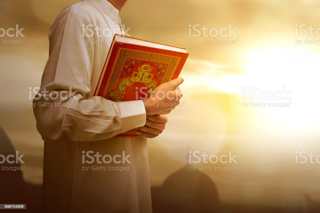 Muslim man in traditional dress holding holy book Koran stock photo