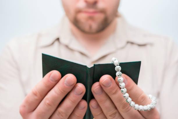 muslim man praying holding a rosary and a koran - sharia foto e immagini stock