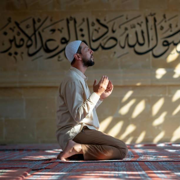 Muslim man praying in mosque stock photo