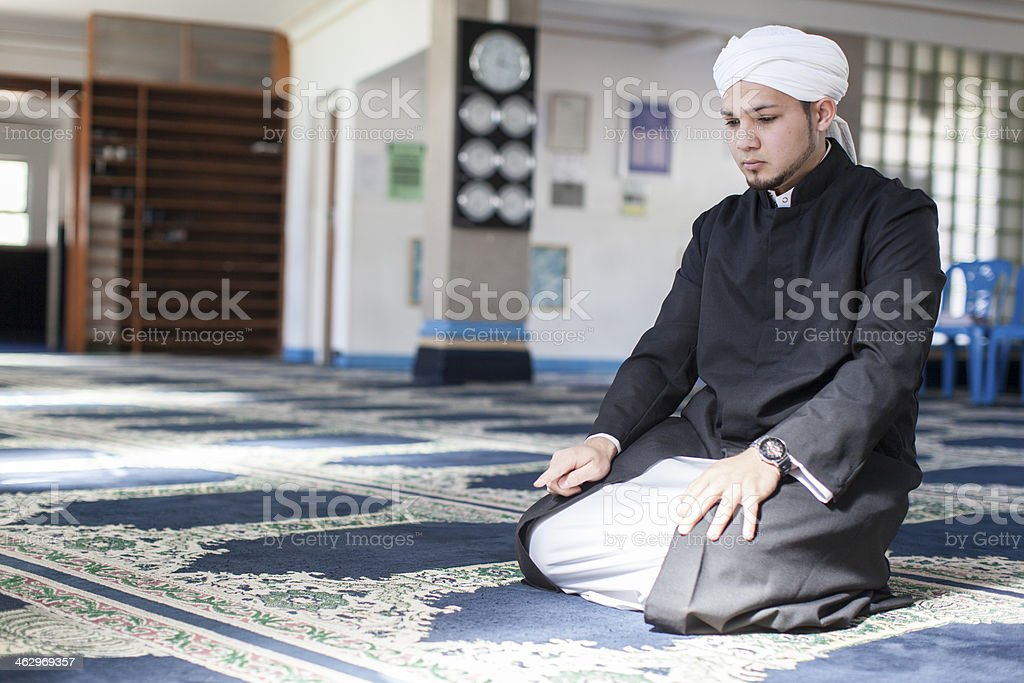 Muslim man praying in the mosque stock photo