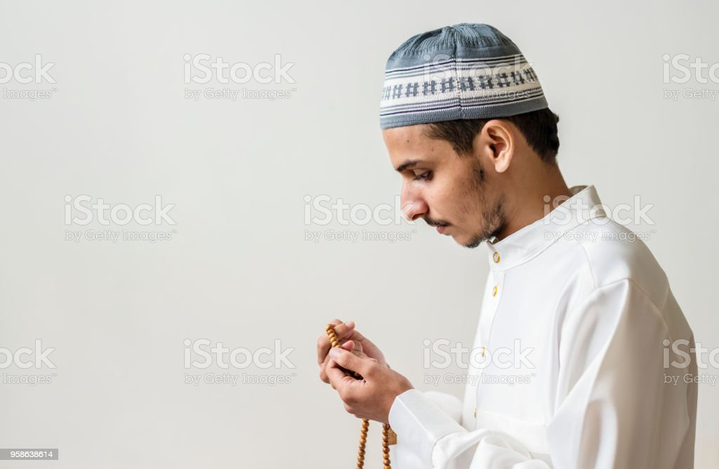 Muslim man praying with tasbih during Ramadan stock photo