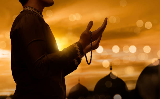 Muslim man raising hand and praying with prayer beads Muslim man raising hand and praying with prayer beads during sunset background alternative pose stock pictures, royalty-free photos & images