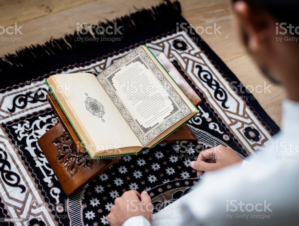 Muslim man studying The Quran stock photo