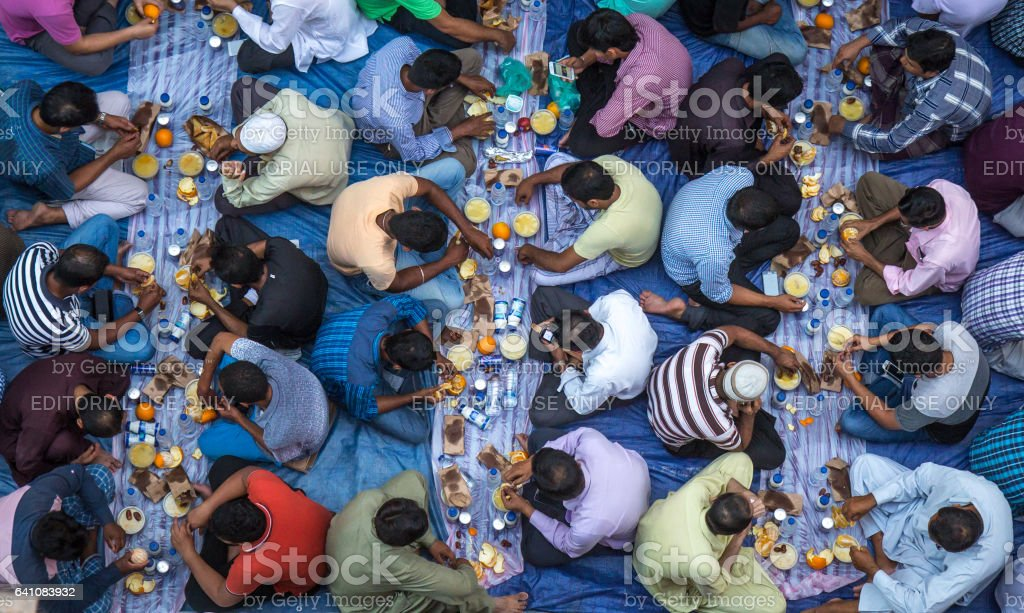 Dubai, UAE - July 16, 2016: Muslim men gathering for a communal charity iftar organised on a street by a local mosque. stock photo