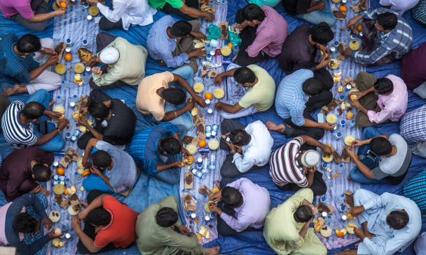 dubai, uae - july 16, 2016: muslim men gathering for a communal charity iftar organised on a street by a local mosque. - ramadan stock photos and pictures