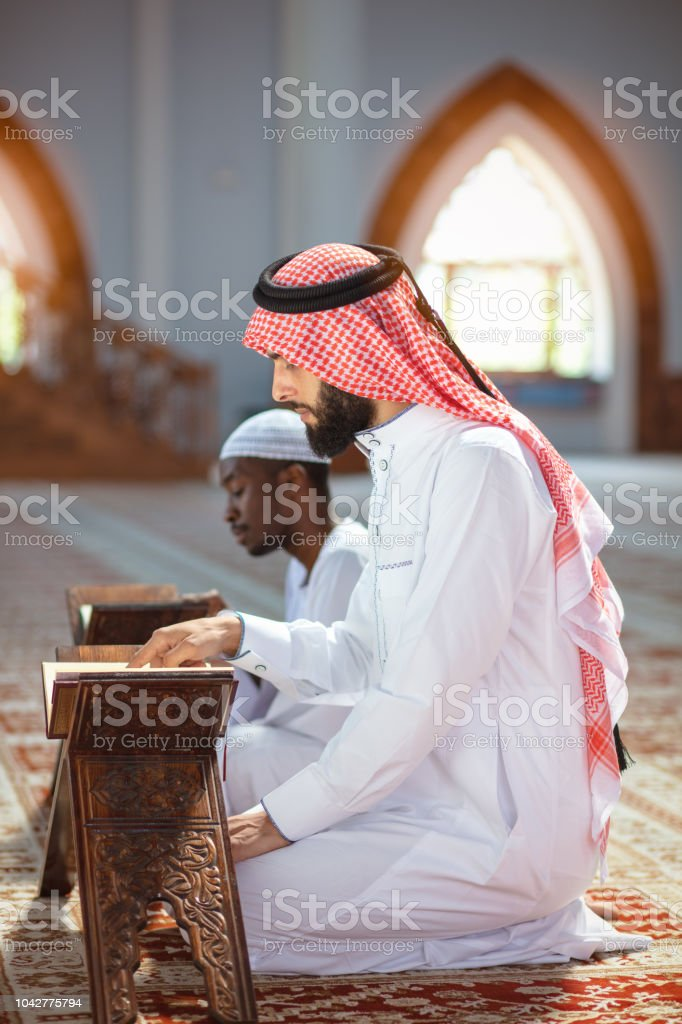Muslim Men Praying With Holy Books In Mosque Stock Photo - Download