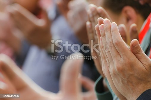 Muslim men praying with lifted hands in Tahrir Square in Cairo, Egypt