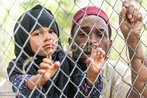 Muslim mid adult refugee black man holding his daughter looking through a fence trying to emigrate to a better future running away from war and violence