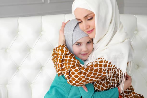 Die muslimische Mama und ihre kleine Tochter in Hijabs umarmen sich auf dem Sofa. – Foto