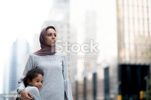 A young muslim mother holds her child closely as they look out at the city. They are wearing casual clothes and the mother is wearing a hijab.