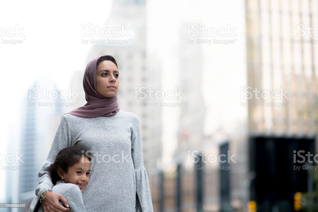 Muslim mother and child hug in the city stock photo