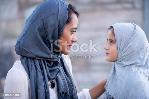 A Muslim woman and her daughter are sitting outdoors closely together wearing traditional head scarves. They are sitting in front of a stone wall. The Mother has her hand on her daughters shoulder and they are sharing a moment of serious conversation.